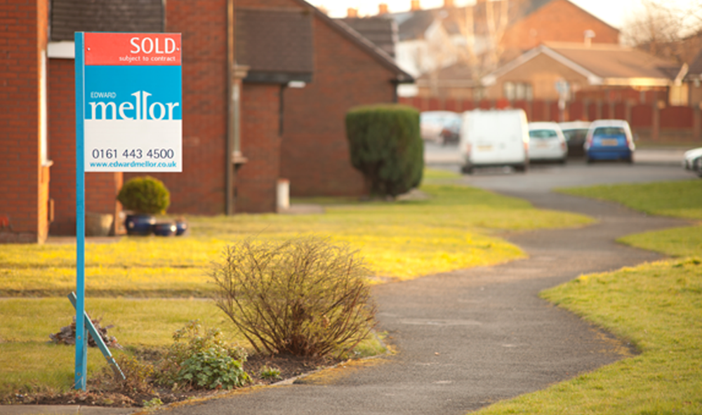 An Edward Mellor for sale sign along a path, with a row of houses.