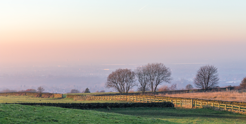 The sunset on Werneth Low over Stockport and Manchester. Including a green field with trees and fences.