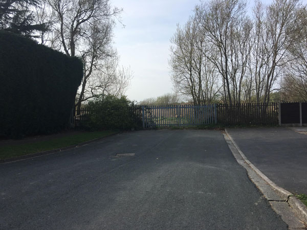 an image of a road with gates in front of woodlands