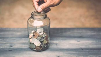 Man putting coins into a jar