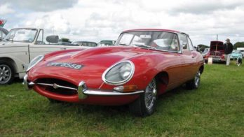 An image of a red Vintage Jaguar in a field