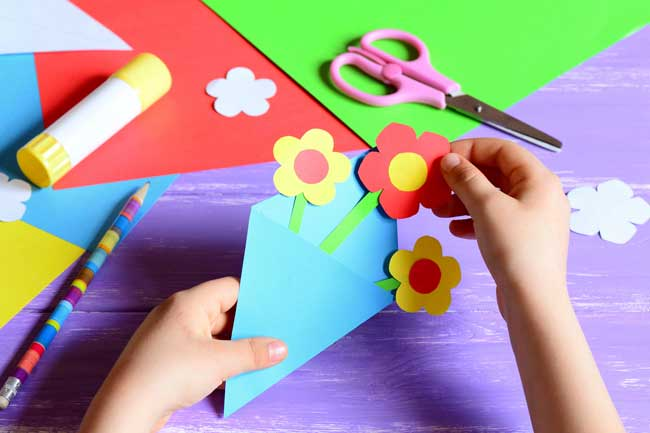 child creating flowers with colourful card
