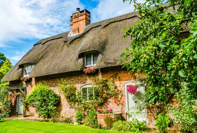 An image of a summer UK cottage with a thatched roof