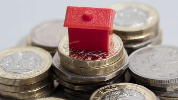 pound coins with small plastic red house